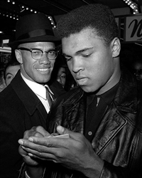 This is a photographic print of Muhammad Ali signing an autograph for Malcolm X